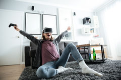 De vrolijke mensenzitting thuis speelt binnen spelen Royalty-vrije Stock Foto's
