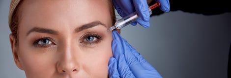De vrolijke middenleeftijdsvrouw krijgt botox procedure royalty-vrije stock fotografie