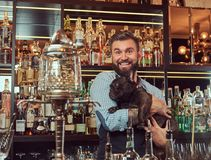 De vrolijke modieuze brutale barman in een overhemd en een schort houdt volbloed- zwarte pug bij bar tegenachtergrond royalty-vrije stock foto