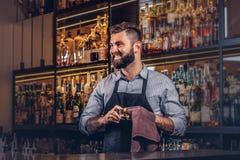 De vrolijke modieuze brutale barman maakt het glas met een doek bij bar tegenachtergrond schoon stock foto's