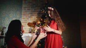 De vrolijke moeder geeft Kerstmis huidig voor haar geliefde dochter Nieuwe jaarnacht bij de voet van de Kerstboom stock videobeelden