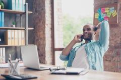 De vrolijke mulatondernemer glimlacht het spreken aan businesspartner over succes van het bedrijf Verhoogd inkomen, is hij gelukk stock afbeeldingen
