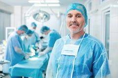 De vrolijke oude chirurg onderzoekt de verrichting royalty-vrije stock afbeelding