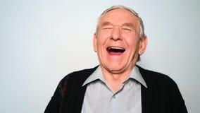 De vrolijke oude mens die isoleert heartily op witte achtergrond lachen stock videobeelden