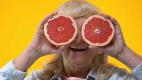 De vrolijke oude voorzijde van de grapefruitplakken van de vrouwenholding van ogen, vruchten voeding stock video