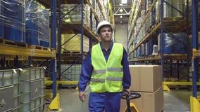 De vrolijke pakhuisarbeider beweegt kar met dozen stock videobeelden