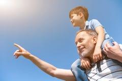 De vrolijke rijpe grootouder onderwijst zijn kleinkind stock foto's