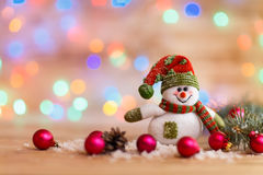 De vrolijke sneeuwman breit hoed en Kerstmis binnen decoratie op festiv Royalty-vrije Stock Afbeeldingen