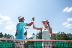 De vrolijke tennisspelers wensen elkaar met succes geluk stock afbeeldingen