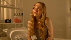 De vrolijke tiener het dromen zitting op bed, onbezorgd positief wijfje, ontspant stock footage