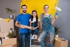 De vrolijke vader, de moeder en weinig dochter maken binnenshuis kleine vernieuwing voor het zetten van het op verkoop stock foto's