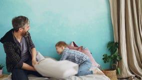 De vrolijke vader volwassen gebaarde mens en speels weinig zoon heeft pret tijdens hoofdkussenstrijd op ware groottebed gelukkig stock video