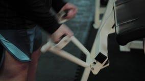 De vrolijke vette mens voert een verkeerde oefening in de gymnastiek uit Voor het eerst in een geschiktheidsclub stock video