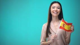 De vrolijke vlag van Spanje van de meisjesholding klaar om vreemde taal, Spaanse school te leren stock footage