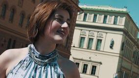 De vrolijke vocalistvrouw presteert in oude stad in de zomerkleding stock videobeelden