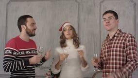 De vrolijke vrienden die van de Kerstmispartij drank hebben en stock videobeelden