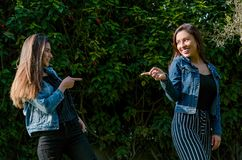 De vrolijke vrienden roddelen in het park De meisjes richten met hun vinger en het lachen stock fotografie