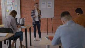 De vrolijke vriendschappelijke leraar communiceert met studenten bij een lezing 4K stock videobeelden