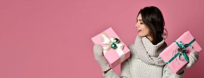 De vrolijke vrouw in grijze sweaterholding houdt twee giften en het hebben van pret stock afbeeldingen