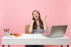De vrolijke vrouw het uitspreiden handen die op mobiele telefoon spreken, die prettig gesprek leiden zitten, werken op kantoor me stock afbeelding