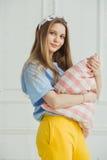 De vrolijke vrouw houdt hoofdkussen in handen Het meisje zonder maakt omhoog Royalty-vrije Stock Foto's