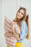 De vrolijke vrouw houdt hoofdkussen in handen Het meisje zonder maakt omhoog Stock Fotografie