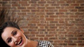 De vrolijke vrouw met donker krullend haar lacht, spelend met haar, het schudden hoofd, die bij camera, baksteenachtergrond lette stock videobeelden