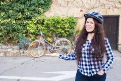 De vrolijke vrouw vertegenwoordigt een bycycle op de achtergrondsteeg royalty-vrije stock afbeeldingen