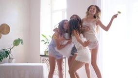 De vrolijke vrouwenvrienden voor de gek houden rond en springen op bed tijdens kippenpartij bij ruimte stock videobeelden
