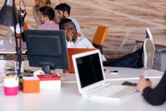 De vrolijke zwarte kerel let op bij het zijn laptop scherm, op zijn het werkplaats, met wapens achter het hoofd royalty-vrije stock afbeeldingen