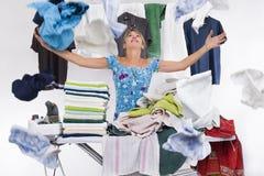 De vrouw achter een strijkplank lanceert hoogste enkel gestreken kleren Stock Afbeelding