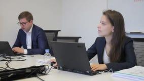 De vrouw achter laptop beantwoordt vragen terwijl het werken in bureau stock video