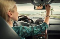 De vrouw in auto kijkt in achteruitkijkspiegel Royalty-vrije Stock Foto's