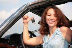 De vrouw in auto toont een sleutel royalty-vrije stock foto