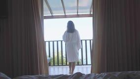 De vrouw in badjas bevindt zich van het bed openend de venstergordijnen en gaat naar overzees meningsterras Jonge vrouwenrek stock footage