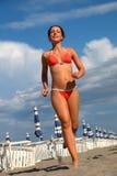 De vrouw in badpak loopt op zand op strand Stock Foto