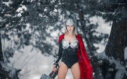 De vrouw in beeld van Germaans-Skandinavische God van donder en onweer bevindt zich met hamer in haar hand Cosplay Royalty-vrije Stock Foto's