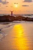 De vrouw begroet zon de overzeese kust Stock Afbeelding