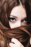 De vrouw behandelt het gezicht door lange bruine haren Stock Fotografie