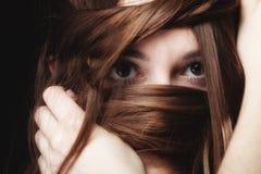De vrouw behandelt het gezicht door lange bruine haren Stock Afbeelding