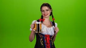 De vrouw in Beiers kostuum danst met een glas bier in de bestelwagen Het groene scherm stock footage