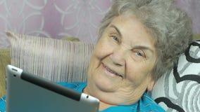 De vrouw bekijkt beelden gebruikend een digitale tablet stock footage