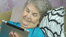 De vrouw bekijkt beelden gebruikend een digitale tablet stock videobeelden