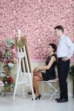 De vrouw bekijkt haar portret en spreekt met kunstenaar stock afbeelding