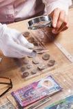 De vrouw bekijkt het Dollarmuntstuk door een vergrootglas Royalty-vrije Stock Foto's