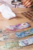 De vrouw bekijkt het Dollarmuntstuk door een vergrootglas Stock Afbeelding