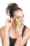 De vrouw bekijkt kiwi met het overdrijven van lens Stock Fotografie