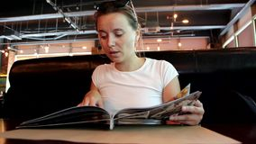 De vrouw bekijkt menu in restaurant, draaiend pagina's stock video