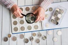 De vrouw bekijkt de muntstukken door een vergrootglas royalty-vrije stock fotografie