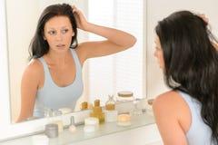 De vrouw bekijkt zich de bezinning van de badkamersspiegel royalty-vrije stock fotografie
